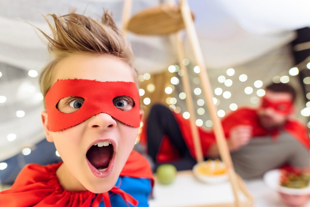 Close-up portrait of excited little boy in superhero costume looking at camera